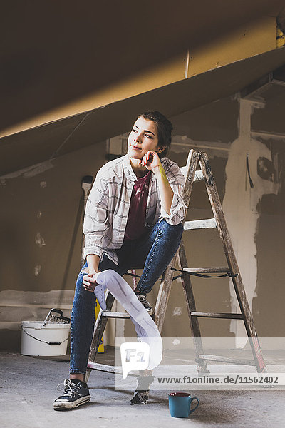 Junge Frau renoviert ihr neues Zuhause  mit Bauplan