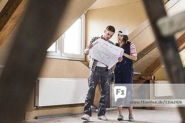 Junges Paar auf der Baustelle seines neuen Zuhauses  Blick auf den Bauplan