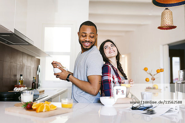 Junges Paar beim Frühstück in der Küche  Rücken an Rücken stehend Junges Paar beim Frühstück in der Küche, Rücken an Rücken stehend