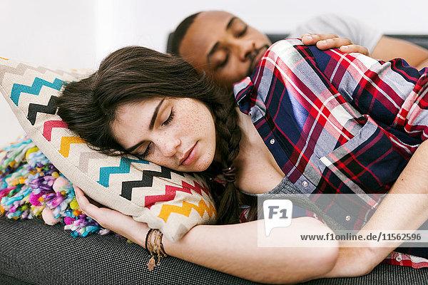 Junges Paar macht ein Nickerchen auf dem Sofa Junges Paar macht ein Nickerchen auf dem Sofa