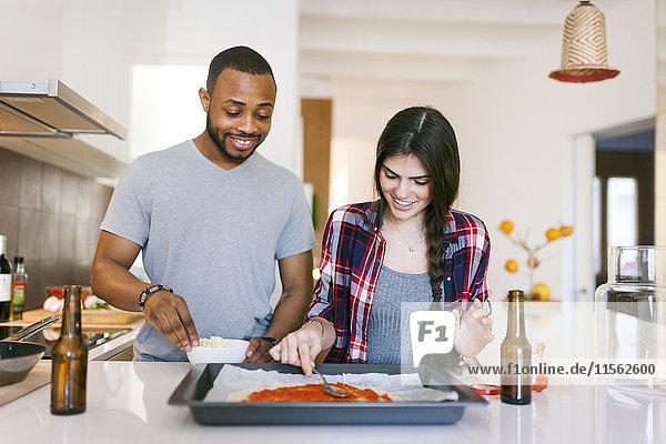 Junges Paar backt Pizza zu Hause