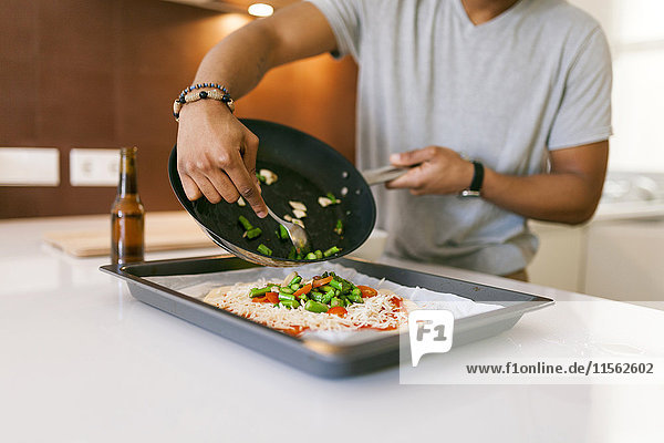 Young man spreading vegetables on pizza dough