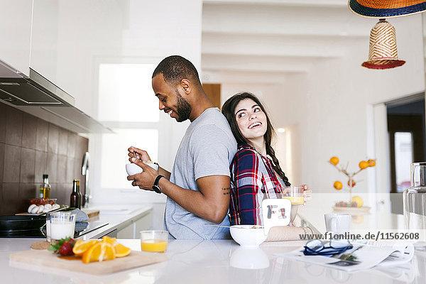 Junges Paar beim Frühstück in der Küche  Rücken an Rücken stehend