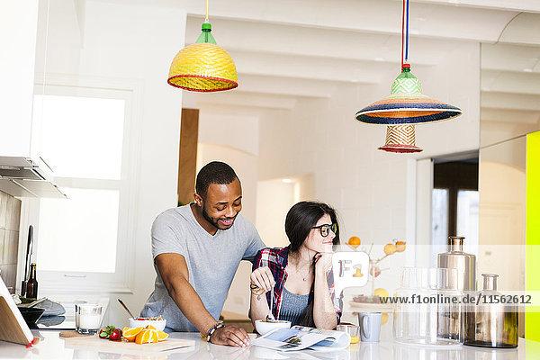 Junges Paar beim Frühstück in der Küche und Lesemagazin Junges Paar beim Frühstück in der Küche und Lesemagazin