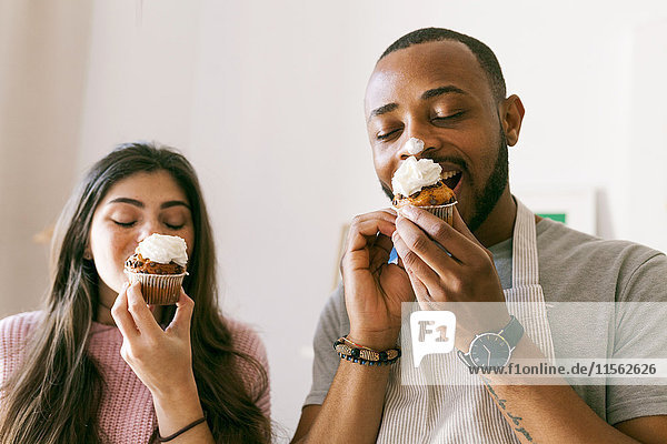 Young couple having fun  eating fresh cupcakes