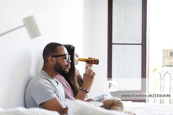 Junges Paar auf dem Bett sitzend  Pizza essend  Bier trinkend