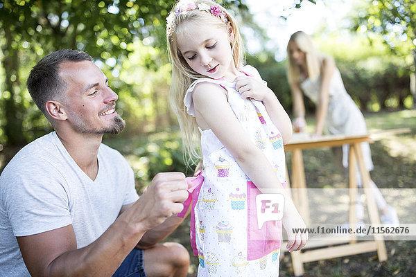 Vater bindet Mädchenschürze im Garten