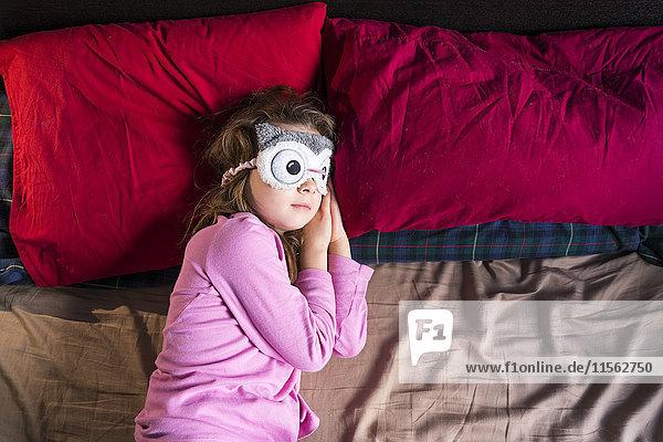Mädchen mit Schlafmaske auf dem Bett liegend