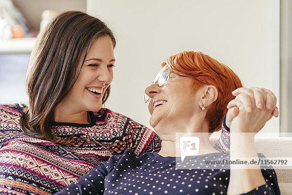 Glückliche erwachsene Tochter mit Mutter zu Hause
