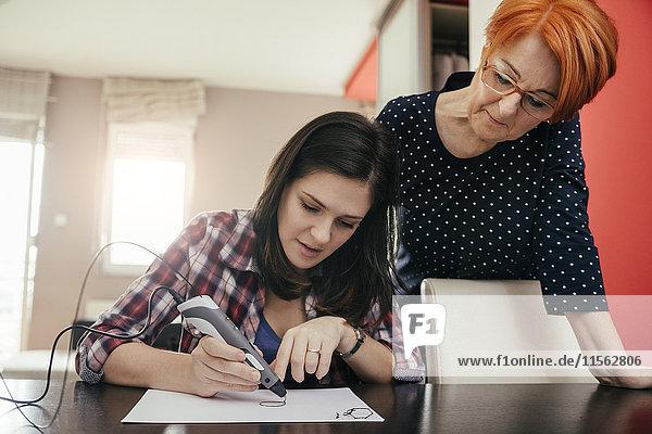Seniorin beobachtet junge Frau beim Zeichnen mit einem 3D-Stift
