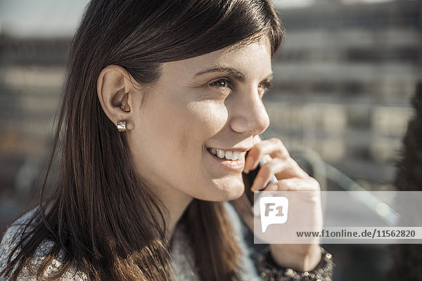 Lächelnde junge Frau mit Hörgerät am Telefon