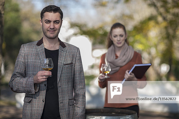 Man and woman with glasses of wine outdoors