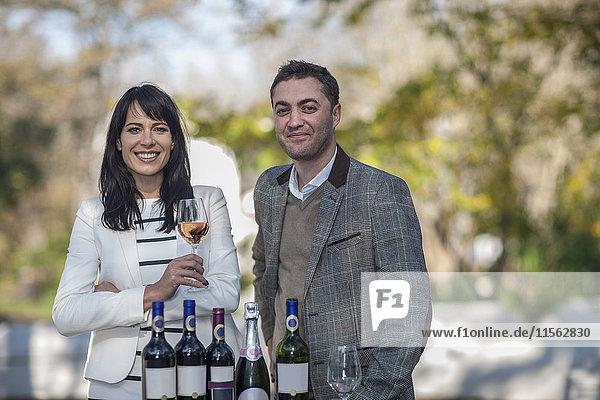 Lächelnder Mann und Frau mit Weinsortiment