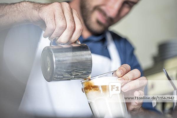Barista zubereitet Latte Macchiato