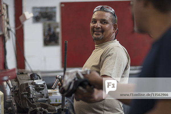Two mechanics working on motorcycle engine in workshop