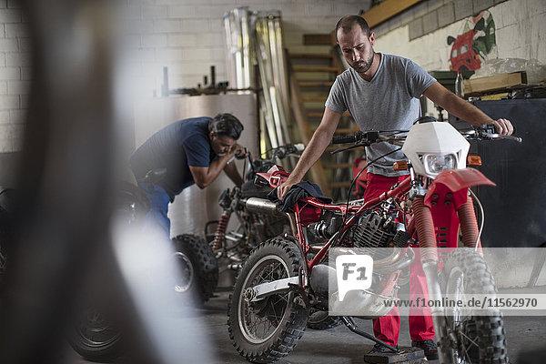 Zwei Mechaniker in der Motorradwerkstatt