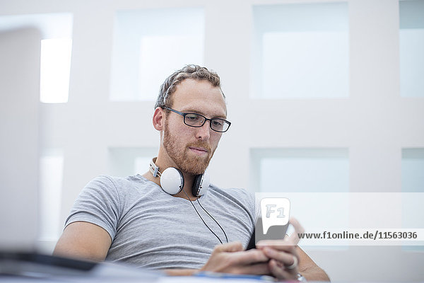 Young man with headphones around his neck reading text messages on his phone