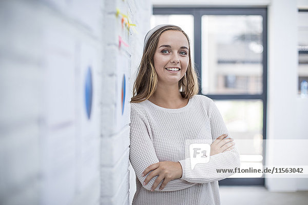 Young woman leaning against wall in office with warmd crossed