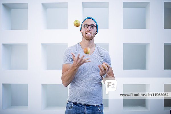 Junger Mann mit Mütze jongliert mit Äpfeln Junger Mann mit Mütze jongliert mit Äpfeln