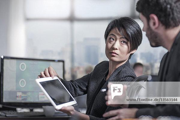 Frau zeigt Tablette an Kollegin im Stadtbüro