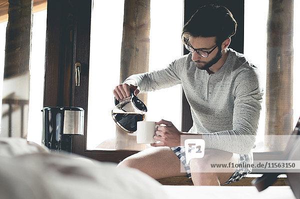 Junger Mann gießt zu Hause Kaffee in die Tasse