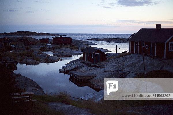 Schweden  Stockholm Archipel  Sodermanland  Huvudskar  Holzhäuser am felsigen Meeresufer bei Sonnenaufgang
