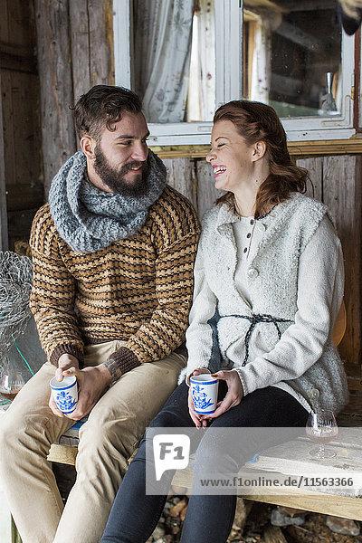 Schweden  Junges Paar auf der Bank sitzend und redend