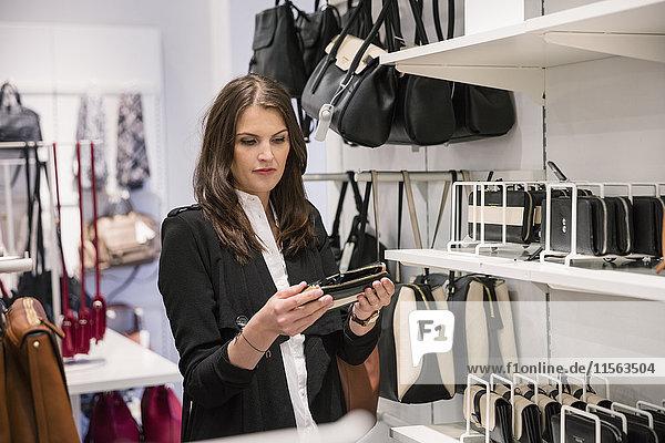 Schweden  Frau wählt Brieftasche im Geschäft
