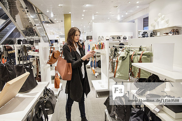 Sweden  Woman photographing clothes in shop