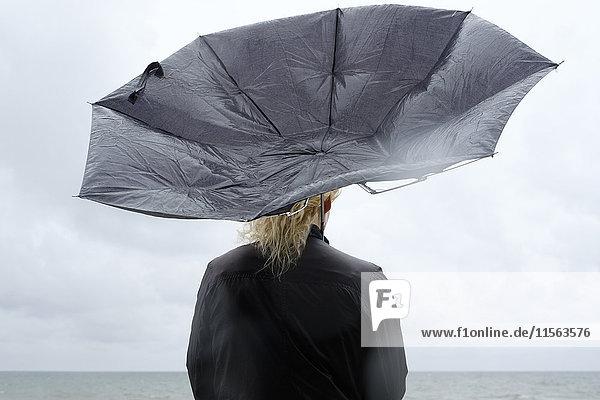 Polen  Niechorze  Frau unter schwarzem Regenschirm beim Beobachten der Ostsee