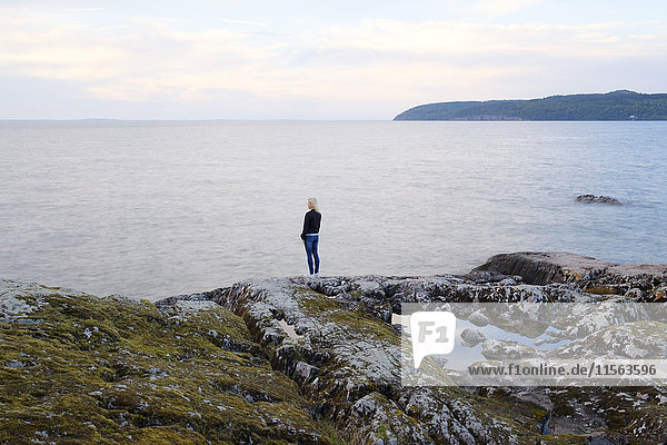 Schweden  Ostergotland  Stora Lund  Frau am Meer stehend und mit Blick auf die Aussicht
