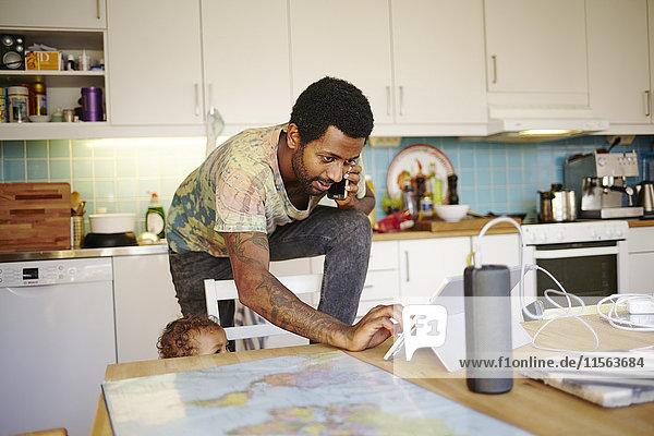 Schweden  Vater mit Sohn (12-17 Monate) in der Küche  mit mobilen Geräten