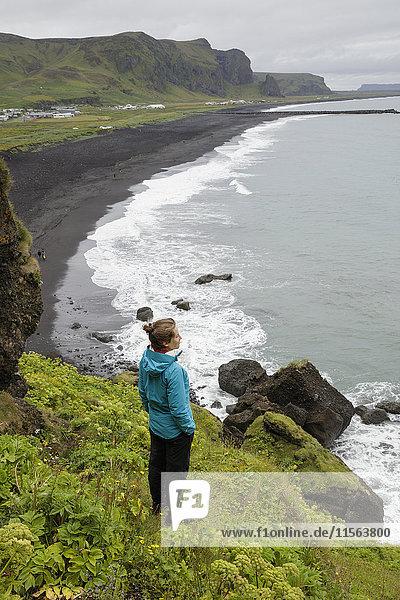 Island  Sudurland  Vik i Myrdal  Wanderer mit Blick vom Kliff auf den schwarzen Sandstrand
