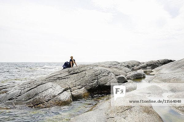 Sweden  Stockholm Archipelago  Sodermanland  Huvudskar  Mature woman sitting on rocky seashore