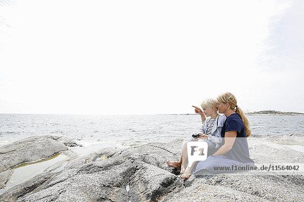 Sweden  Stockholm Archipelago  Sodermanland  Huvudskar  Mother and son (6-7) sitting on rocky seashore