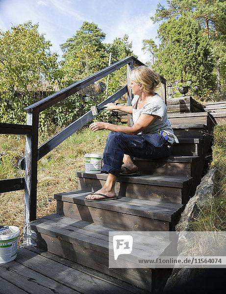 Sweden  Stockholm Archipelago  Sodermanland  Orno  Mature woman painting wooden railing