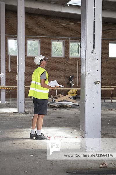 Schweden  Mann steht auf der Baustelle und hält Papiere in der Hand