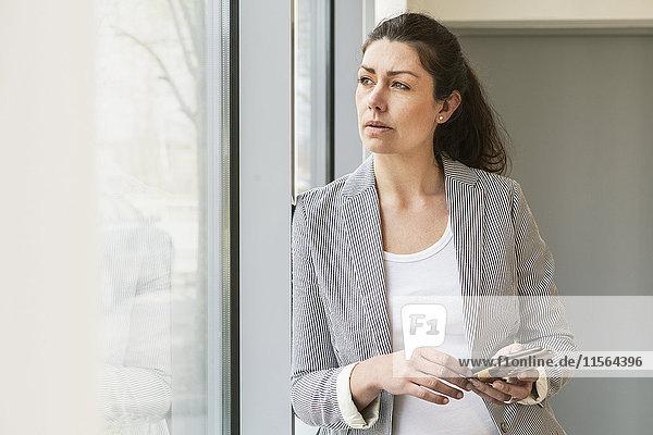 Schweden  Geschäftsfrau beim Blick durchs Fenster