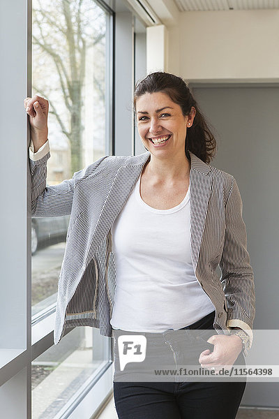 Sweden  Businesswoman standing at window and smiling