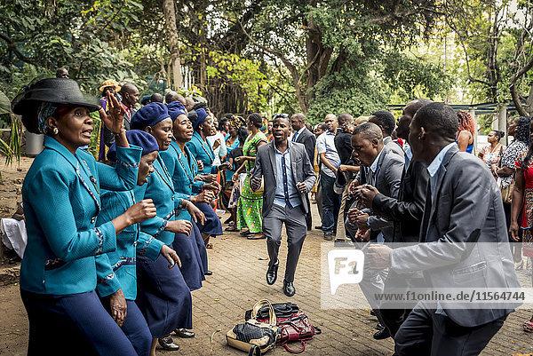 'Wedding guests celebrating in Tunduru Botanical Gardens  designed in 1885 by British gardener Thomas Honney; Maputo  Mozambique'