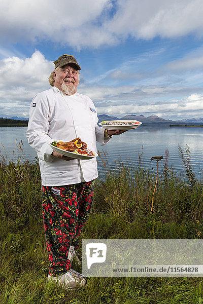 Tikchik Narrows Lodge Chef  Matt Spence  holding his Peking Duck and Sushi rolls on the shore of Tikchik Lake  Wood-Tikchik State Park  Southwest Alaska  USA