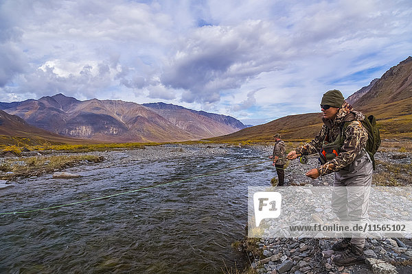 Two men fly fishing for arctic grayling on the Atigun River north of Atigun Pass along the Dalton Highway  Interior Alaska  USA