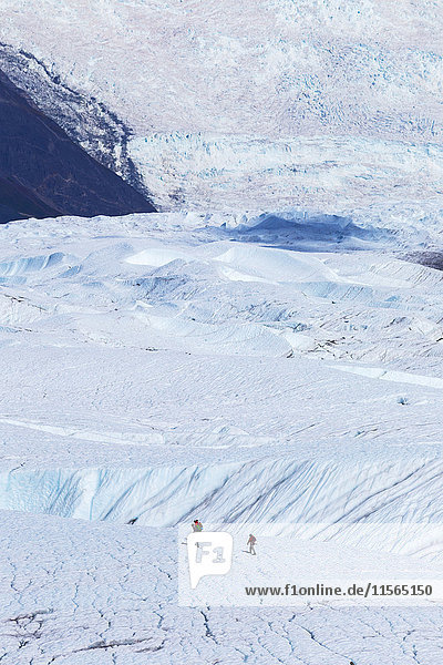 People cross Root Glacier in Wrangell-St. Elias National Park to participate in guided ice climbing with the Stairway Icefall is in the background  Southcentral Alaska  USA