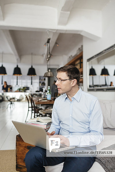 Deutschland  Mann mit Laptop zu Hause