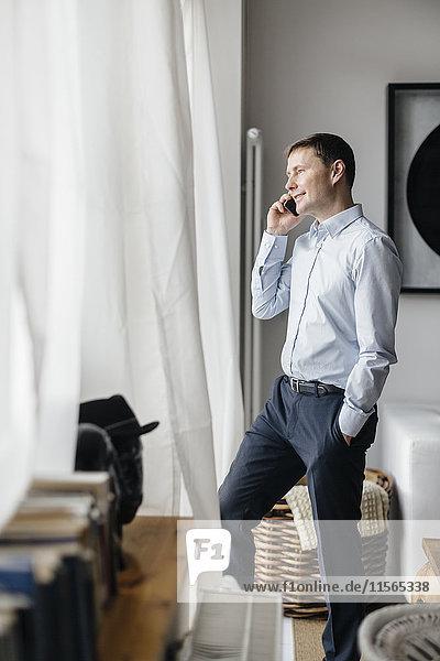 Deutschland  Mann mit Handy am Fenster