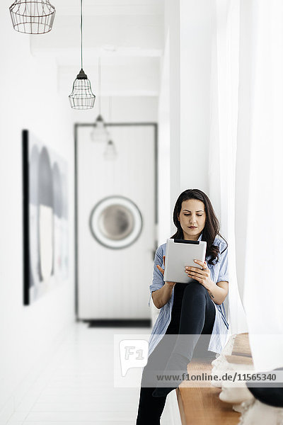 Germany  Woman sitting on window sill and using tablet