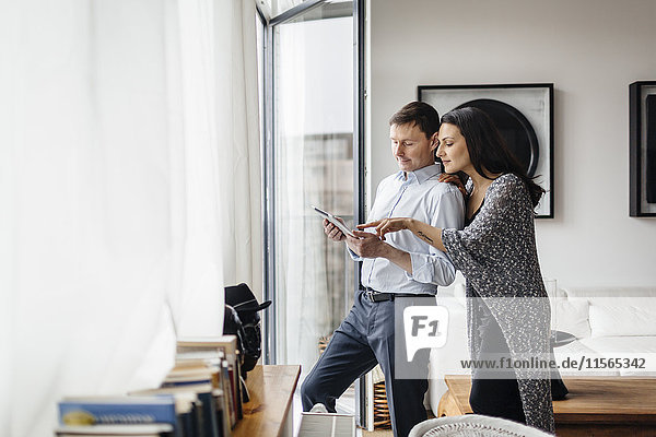 Germany  Couple using tablet by window
