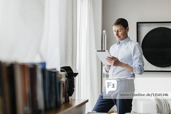Deutschland  Mann mit Tablette am Fenster