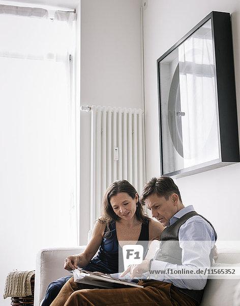 Deutschland  Paar sitzend auf Sofa und Lesebuch