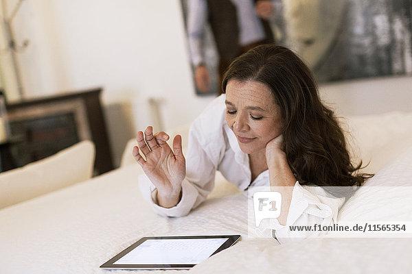 Deutschland  Frau auf dem Bett liegend und mit Tablette